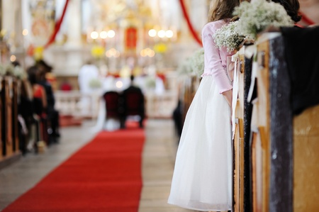 Girl in a white dress watching wedding ceremony photo