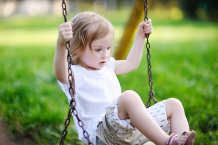 Adorable little girl having fun on a swing photo