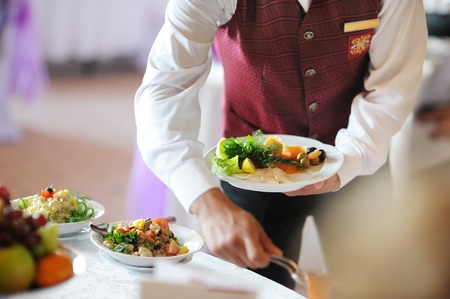Waiter carrying a plate with meat dish photo