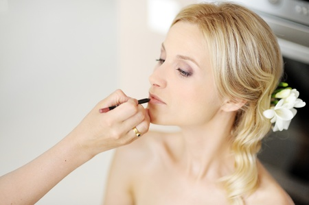 natural make up: Young beautiful bride applying wedding make-up by make-up artist