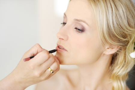 makeup a brush: Young beautiful bride applying wedding make-up by make-up artist