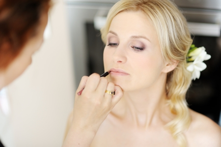 make-up poeder: Jonge mooie bruid toe te passen bruiloft make-up door de make-up artist