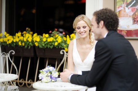 Bride and groom drinking coffee at an outdoor cafe photo