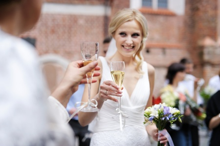 Bride is holding champagne glass after a wedding ceremony photo