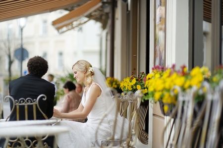 Bride and groom drinking coffee at an outdoor cafe Stock Photo - 12789280