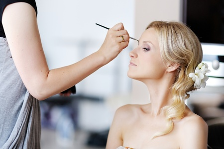 beauty make up: Young beautiful bride applying wedding make-up by make-up artist
