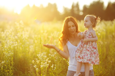 Young mother holding her adorable toddler girl at sunset Stock Photo - 12791430