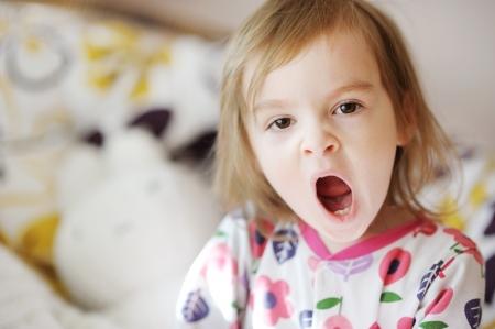 Little yawning toddler girl in pajamas on sunny morning