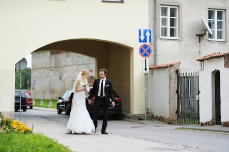 Bride and groom having fun in an old town photo