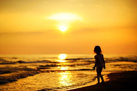 A child as silhouette by the sea photo