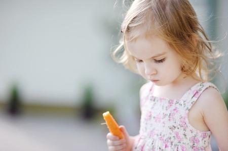 niños comiendo: Adorable feliz preescolar niña come la zanahoria al aire libre Foto de archivo