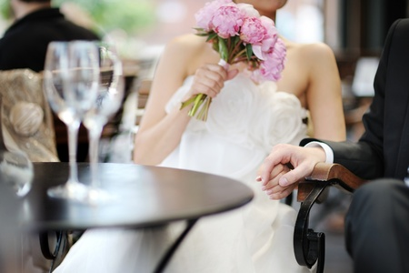Bride and groom holding their hands in an outdoor cafe photo