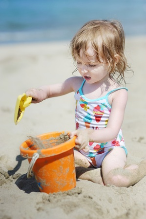 Cute little girl playing with beach toys on a beach photo