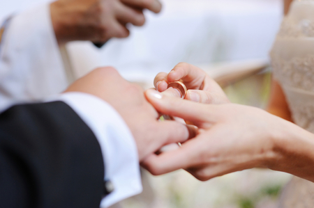 Bride putting a wedding ring on groom's finger 스톡 콘텐츠