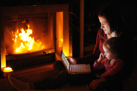 fireplace family: Young mother and daughter by a fireplace with a laptop