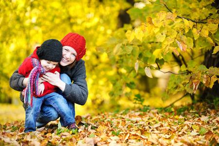 otoño: Madre joven y su muchacha del niño se divierten en otoño