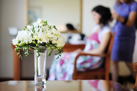 'getting ready': Bridal bouquet and a bride getting ready on a background