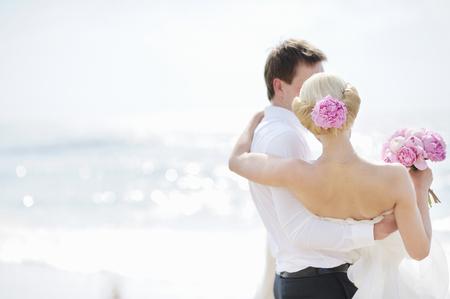nude bride: Beach wedding: bride and groom by the sea