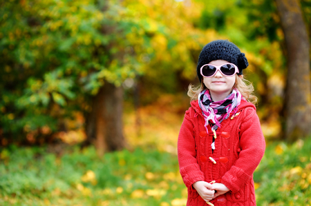little colours: Adorable little girl in sunglasses on beautiful autumn day Stock Photo