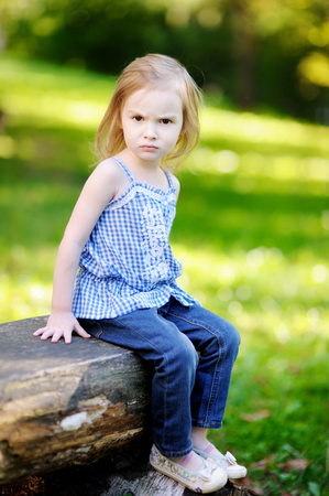 dissapointed: Angry little girl portrait outdoors Stock Photo