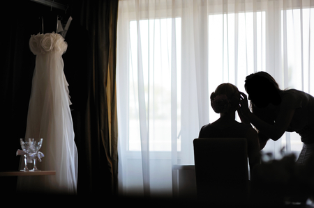 Silhouettes of a bride applying make-up and a make-up artist