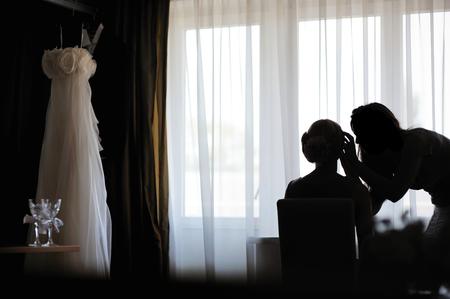 mujer maquillandose: Siluetas de una novia de aplicar el maquillaje y un artista de maquillaje Foto de archivo