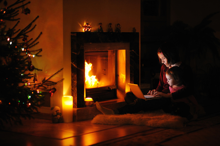 dark room: Young mother and daughter by a fireplace on Christmas Stock Photo