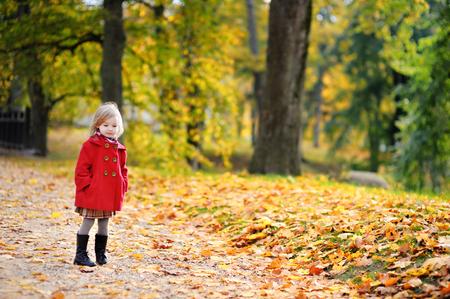 jolie petite fille: Petite fille dans un manteau rouge à l'automne