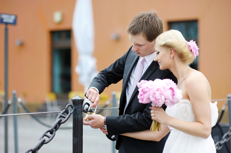 Beautiful bride and groom hanging lucky lock on a bridge photo