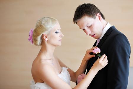 adjusting: Beautiful bride adjusting grooms boutonniere Stock Photo
