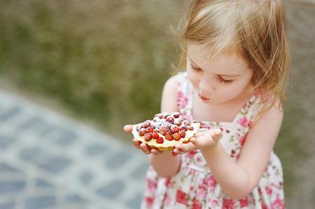 Little girl eating a strawberry tart outdoors Stock Photo