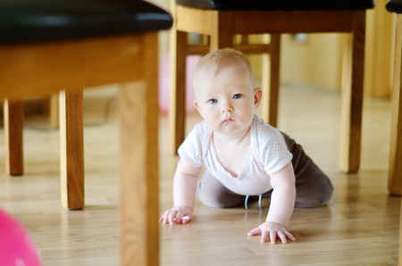 crawling baby: Adorable crawling baby girl under a table