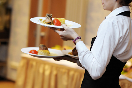 catering service: Waitress is carrying three plates with meat dish Stock Photo