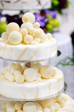 wedding table decor: Fancy delicious white and yellow wedding cake Stock Photo