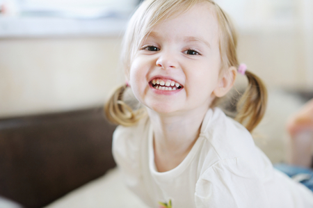 indoors: Adorable little girl laughing indoors