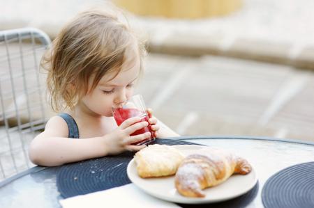 eating breakfast: Smiling little girl having breakfast outdoors