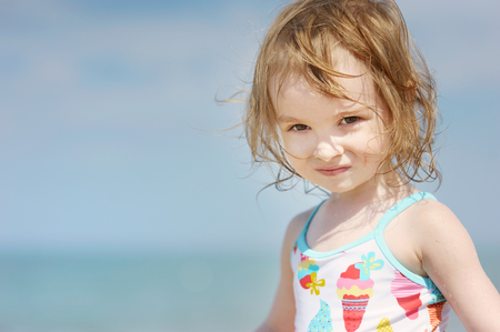 Cute little girl playing on a beach photo