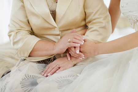 put on: Bride and her mother holding hands before wedding ceremony Stock Photo