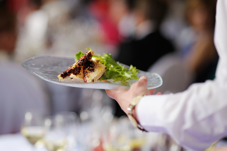waiter: Waitress is carrying a plate with meat dish