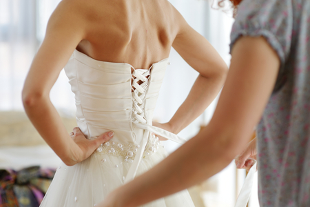 put: Helping the bride to put her wedding dress on Stock Photo