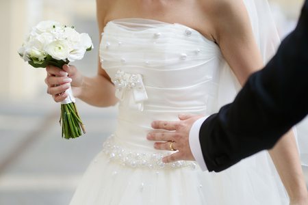 ring finger: Bride is holding a wedding bouquet