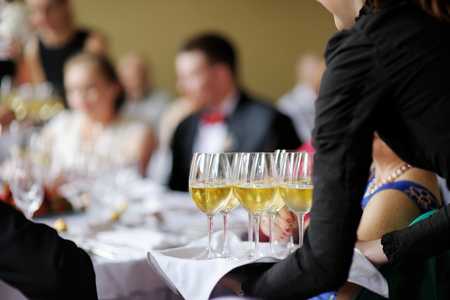 waiter: Waitress with dish of champagne and wine glasses Stock Photo