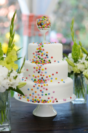 wedding table decor: Delicious white wedding cake decorated colorful candies
