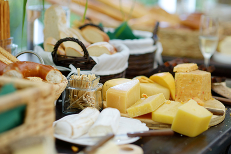 pan y vino: Queso y surtido de pan en una mesa Foto de archivo
