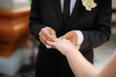 black hand: Groom is putting the ring on brides finger