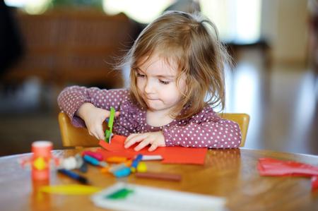 Little preschooler girl cutting colorful paper