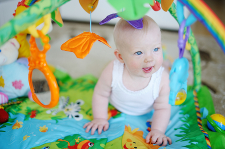 playmat: Baby girl playing with soft toys Stock Photo