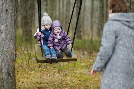 2 november: Two sisters swinging outdoors on early spring or late autumn