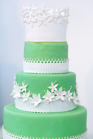 wedding food: Green wedding cake decorated with sugar white flowers Stock Photo
