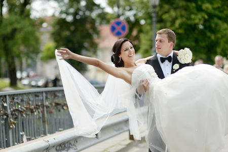 Groom carrying his beautiful bride photo